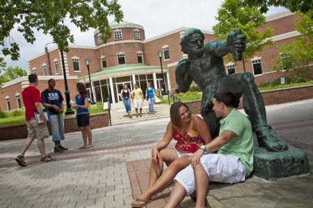 Students lounge near a statue on the Florham Campus quad in the spring.